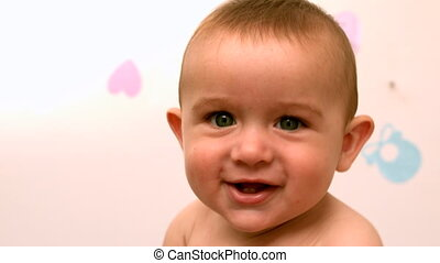 Baby sitting in crib smiling at cam