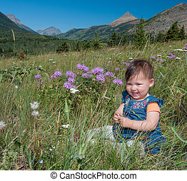 Baby Sitting in Grass With Flowers