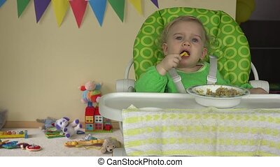 baby sitting in high chair with spoon and plate and toys...
