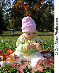 baby sitting in leaves