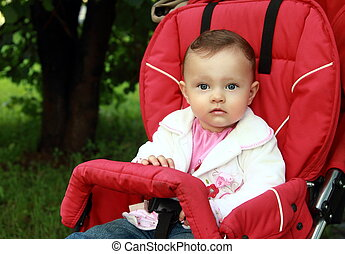 Baby sitting in stroller with fun look on summer green background