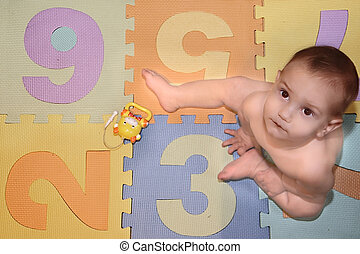baby sitting on background with numbers