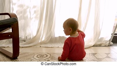 Baby sitting on floor near window - Back view of...