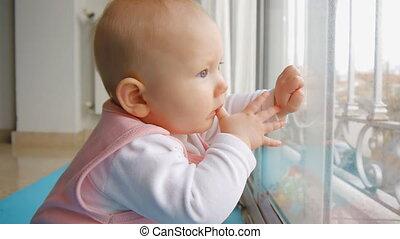Baby sitting on floor near window thumb-sucking.