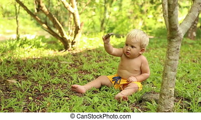 baby sitting on grass and digging in ground