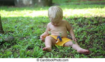 baby sitting on grass and exploring vegetation
