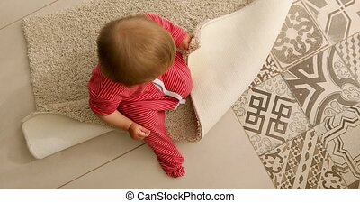 Baby sitting on rug - From above of unrecognizable baby in...