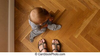 Baby sitting on wooden floor - From above curious baby...