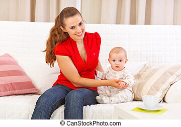 Baby sitting with mother on sofa