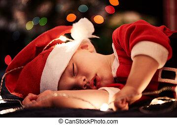 Baby sleeping in santa outfit for christmas season near tree