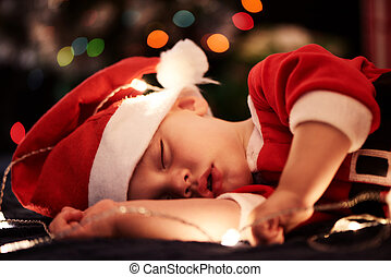 Baby sleeping in santa outfit for christmas season near tree