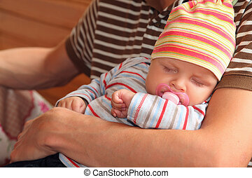 baby sleeping on hands of man