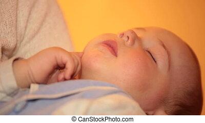 Baby sleeping on mother's hands