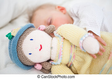 Baby sleeping while holding a plush doll in a bedroom