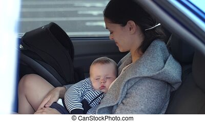 Baby sleeps in a car on a mother's hands