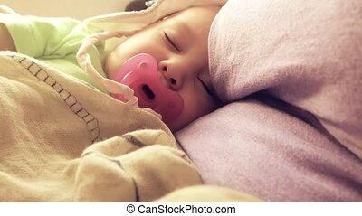 Baby sleeps with pacifier while traveling by plane - Mum and...