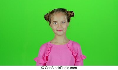 Baby smiles and looks into the distance, covering her face with her hands. Green screen
