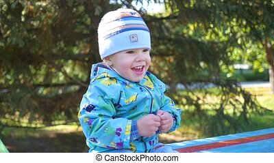 baby smiling in a Park sitting on the bench