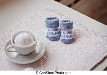 baby socks and ball of yarn in white coffee Cup on the table