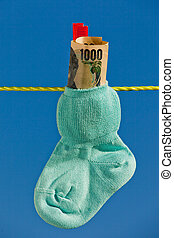 baby socks on clothesline with yen bills - baby socks on...