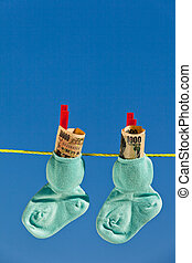 baby socks on clothesline with yen banknotes - baby socks on...