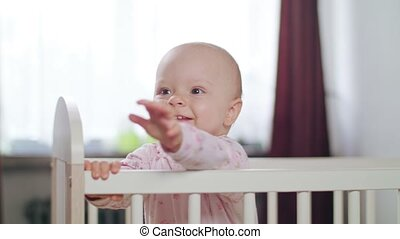 Baby Standing in a Crib at Home