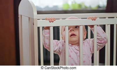Baby Standing in a Crib at Home. Crying