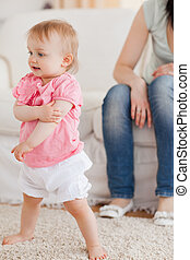 Baby standing on a carpet while her mother is sitting on a...