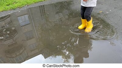 Baby stomping through puddles in yellow rubber boots - Baby...
