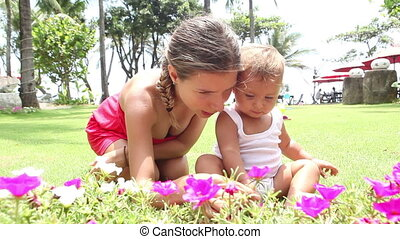 baby studying flowers - young mother showing flowers to her...