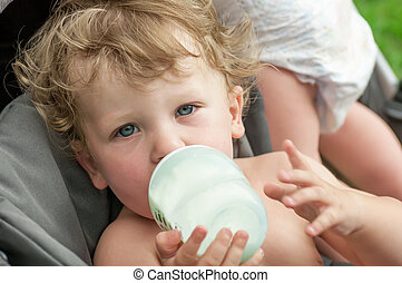 baby sucking on a bottle of porridge sitting in a wheelchair
