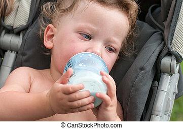 baby sucks a bottle with milk