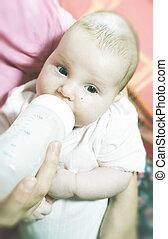 Baby sucks on a bottle