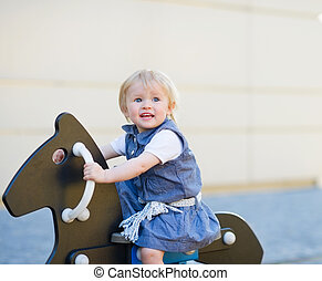 Baby swing on horse on playground. Side view