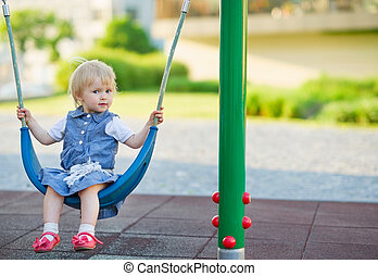 Baby swinging on swing on playground. Side view