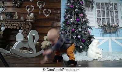 Baby takes its first steps to her mother in the studio with Christmas decor