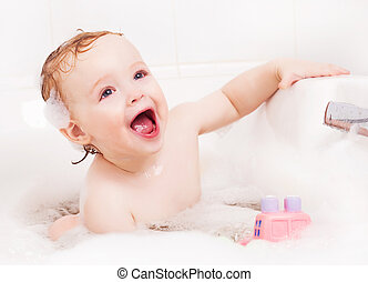 baby taking a bath - cute one year old boy taking a relaxing...