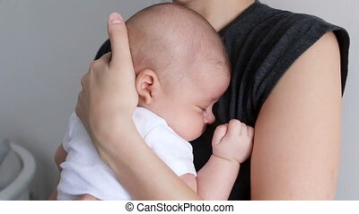 baby the boy is sleeping on the mother's arms