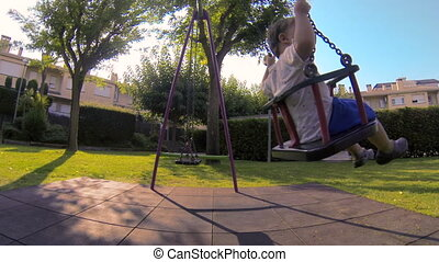 Baby Toddler in the Park Swing 01. - Child playing in the...