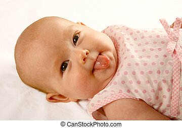 Baby Tongue - A baby girl lying on her back sticking out her...