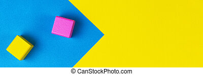 Baby toys banner background. Wooden colorful blocks on geometric yellow and blue background. Top view, flat lay