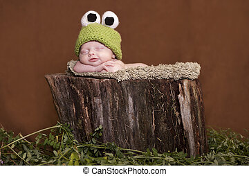 Newborn baby dressed up like tree frog and smiling