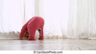 Funny kid in red pajamas bending and standing upside down on floor and looking back at home