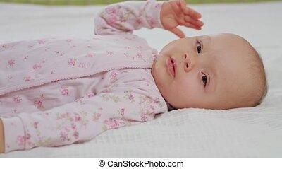 Baby Waking Up From Sleep - A baby waking up from sleep on a...