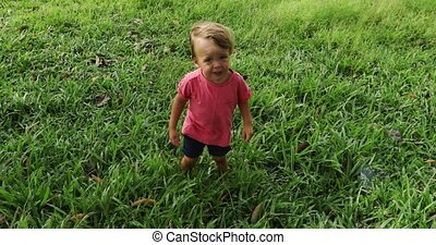 Baby walking on green grass