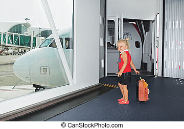 Baby walks for boarding to flight in airport departure gate...