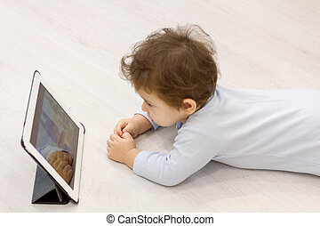baby watching cartoons on her tablet computer in the background of the toys he child does not want to play