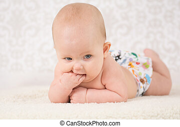 Baby in a reusable nappy, lying on a belly on a light background, bitting her fist