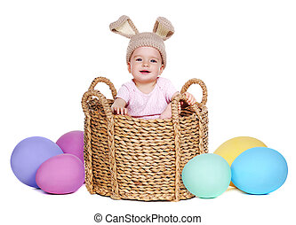 baby wearing rabbit hat sitting in a basket with giant easter eggs