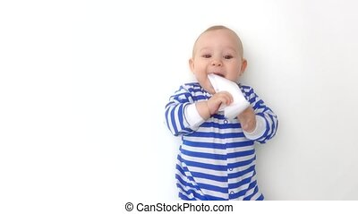 Baby wearing striped romper plays with paper boat - Cute...